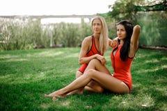 Due ragazze che si siedono sull'erba verde in costumi da bagno immagini stock