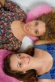 Due ragazze che si trovano sui cuscini e che smilling vago fotografia stock libera da diritti