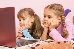 Due ragazze che si trovano sul suo stomaco sul letto che esamina lo schermo del computer portatile Fotografia Stock