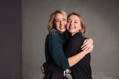 Due ragazze che stanno insieme, abbraccianti, ridenti e sorridenti Lo studio sparato nella parete grigia Fotografie Stock