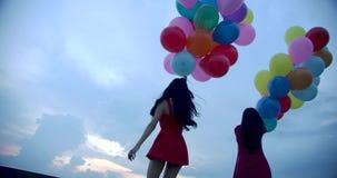 Due ragazze che tengono pallone con il fondo del cielo video d archivio