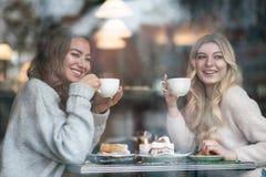 Due ragazze che trinking il caffè nel caffè e passano insieme il tempo Fotografia Stock Libera da Diritti