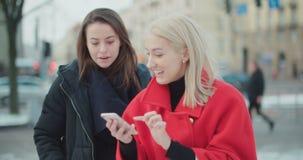 Due ragazze che utilizzano telefono cellulare in una città video d archivio