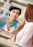 Due ragazze comunicano la seduta alla tabella Immagini Stock Libere da Diritti