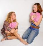 Due ragazze con i cuori molli fotografie stock