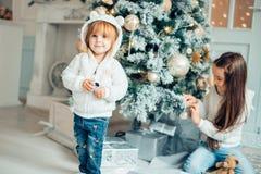 Due ragazze con il cappello di Santa che pone davanti all'albero di Natale Fotografia Stock Libera da Diritti