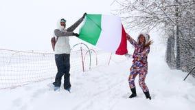 Due ragazze con la bandiera dell'Italia sul pendio dello sci video d archivio