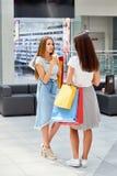 Due ragazze con la chiacchierata dei sacchetti della spesa Fotografie Stock