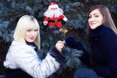 Due ragazze con Santa e gli sparklers fotografie stock