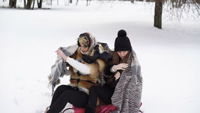 Due ragazze coperte in plaid caldo che si siede nell'inverno parcheggiano 4K stock footage