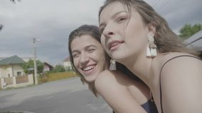 Due ragazze degli studenti che viaggiano in macchina che va sul gioco di vacanza peso dalla finestra divertendosi e sentendosi li archivi video