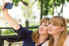 Due ragazze dei gemelli che prendono selfie in ristorante Fotografia Stock Libera da Diritti