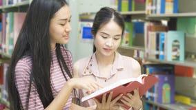 Due ragazze dell'adolescente hanno letto un libro allo scaffale di libro nel fondo Fotografie Stock
