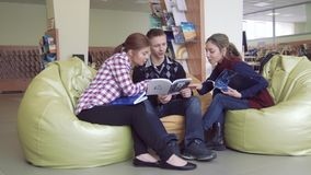 Due ragazze dell'università e un ragazzo che guarda attraverso i libri interessanti stock footage