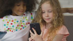 Due ragazze della scuola materna che per mezzo degli smartphones per spendere tempo libero, i bambini e tecnologia archivi video