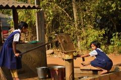 Due ragazze della scuola primaria stanno lavando la loro mano ed i loro piatti prima della presa del pasto di mezzogiorno in una  fotografia stock libera da diritti
