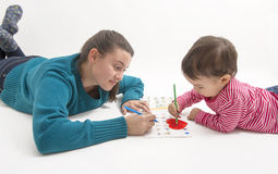 Due ragazze delle età differenti che si trovano sul pavimento e sul disegno Fotografie Stock Libere da Diritti