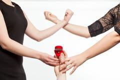 Due ragazze di gelosia che combattono per un anello che è tenuto dall'uomo immagine stock