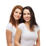 Due ragazze di risata nell'abbracciare bianco delle magliette Fotografia Stock