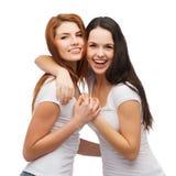 Due ragazze di risata nell'abbracciare bianco delle magliette Immagine Stock