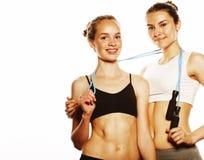 Due ragazze di sport che si misurano hanno isolato su bianco immagini stock