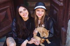 Due ragazze di via con un gatto Fotografie Stock Libere da Diritti