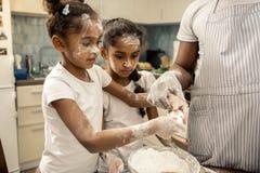 Due ragazze divertenti con le acconciature piacevoli che cucinano insieme a fine settimana immagini stock
