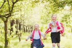 Due ragazze divertenti della scuola che dirigono tenersi per mano all'aperto fotografie stock libere da diritti