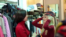 Due ragazze divertenti scelgono i vestiti nel deposito Acquisto Comperando sul sito video d archivio