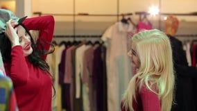 Due ragazze divertenti scelgono i vestiti nel deposito Acquisto Comperando sul sito stock footage