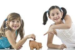 Due ragazze e banca piggy Fotografie Stock Libere da Diritti