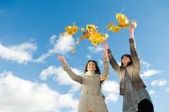 Due ragazze e fogli di autunno Fotografie Stock Libere da Diritti