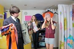 Due ragazze e un buy dell'uomo ad un cappello della ragazza immagine stock libera da diritti
