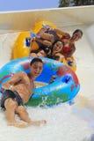 Due ragazze ed azionamenti allegri del ragazzo con il tubo sul rafting fanno scorrere Fotografia Stock