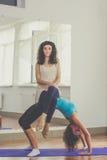 Due ragazze esili stanno facendo il acroyoga in studio Immagini Stock Libere da Diritti