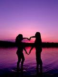 Due ragazze fanno la forma di cuore Fotografia Stock Libera da Diritti