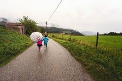 Due ragazze fatte funzionare nella pioggia con il loro ombrello immagine stock