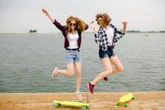 Due ragazze felici allegre del pattinatore in attrezzatura dei pantaloni a vita bassa divertendosi su un pilastro di legno durant fotografia stock libera da diritti
