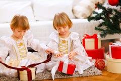 Due ragazze felici che aprono i regali si avvicinano all'albero di Natale Fotografia Stock Libera da Diritti