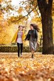 Due ragazze felici che corrono nel parco della città di autunno immagine stock libera da diritti