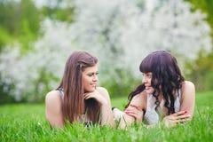 Due ragazze felici che giocano nell'erba verde su un fondo di un albero di fioritura Fotografie Stock