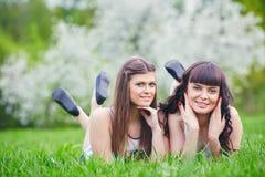 Due ragazze felici che giocano nell'erba verde su un fondo di un albero di fioritura Immagini Stock