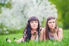 Due ragazze felici che giocano nell'erba verde su un fondo di un albero di fioritura Immagine Stock Libera da Diritti
