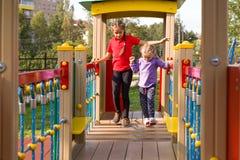Due ragazze felici che giocano sul campo da giuoco, camminanti sui punti d'oscillazione e provanti al keeep il loro equilibrio fotografia stock libera da diritti
