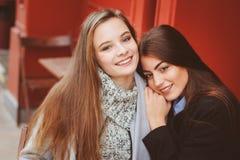 Due ragazze felici che parlano e che bevono caffè nella città di autunno in caffè Riunione di buoni amici, giovani studenti alla  Fotografia Stock Libera da Diritti