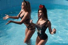Due ragazze felici godono di di nuotare nello stagno Immagine Stock Libera da Diritti
