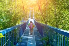 Due ragazze felici piccole camminano lungo un ponte di attaccatura un giorno soleggiato fotografia stock libera da diritti