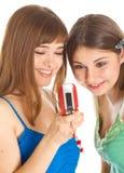 Due ragazze graziose che leggono SMS sul telefono mobile Fotografie Stock Libere da Diritti