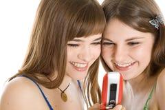 Due ragazze graziose che leggono SMS sul telefono mobile Fotografia Stock