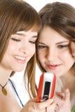 Due ragazze graziose che leggono SMS sul telefono mobile Immagine Stock Libera da Diritti